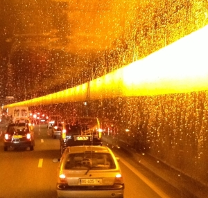 Light reflected on raindrops on the windshield of the bus, along with the blurred lights in the tunnel.