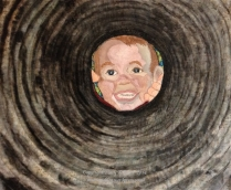 """Look, Mom! (28""""w x 21""""h) 2014 A young mother's quick shot of her son calling her, like he does several dozen times a day, results in a truly whimsical view of his round little face framed by the culvert that runs under their driveway. Painting the circular rings on batik fabric with fabric dyes created the circular shape of the culvert, along with quilting to emphasize the tunnel effect. The face is pieced and then embroidered, and a touch of fabric paint is added for the finish. This piece is inspired by a photograph taken by Kristi Enevoldsen, mother of the little boy, Dalton."""