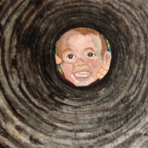 "Look, Mom! (28""w x 21""h) 2014 A young mother's quick shot of her son calling her, like he does several dozen times a day, results in a truly whimsical view of his round little face framed by the culvert that runs under their driveway. Painting the circular rings on batik fabric with fabric dyes created the circular shape of the culvert, along with quilting to emphasize the tunnel effect. The face is pieced and then embroidered, and a touch of fabric paint is added for the finish. This piece is inspired by a photograph taken by Kristi Enevoldsen, mother of the little boy, Dalton."